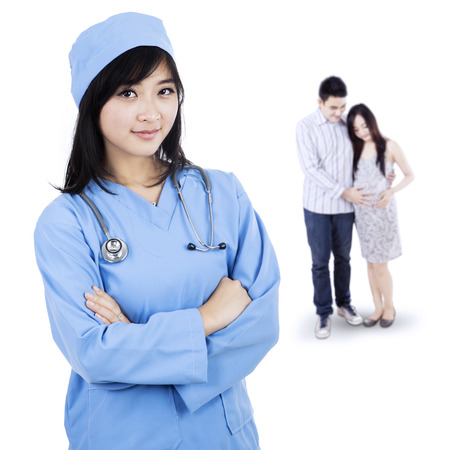 Smiling female doctor standing in front of a pregnant woman and her husband photo