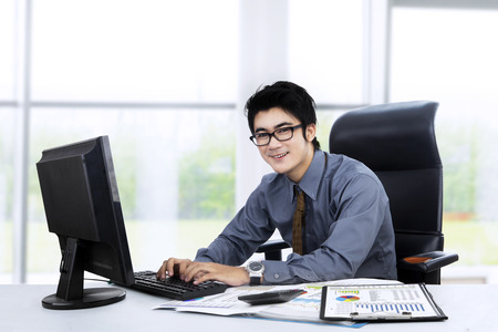 Portrait of young manager working at office while typing on keyboard photo