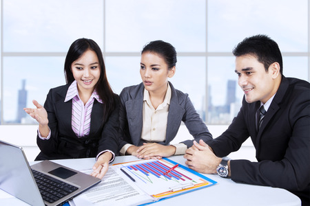 A business team of three people having a meeting in office photo