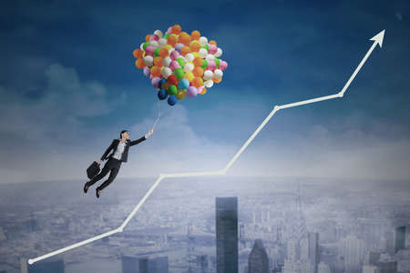 sales occupation: Young businesswoman flying with balloons over upward arrow symbolizing growing business Stock Photo