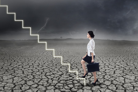 crack climb: Businesswoman walking up on stairs in stormy weather
