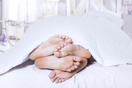 Close-up of couples feet cuddling. shost at bedroom photo