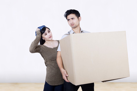 insecure: Asian couple confused of something while carry box at new home