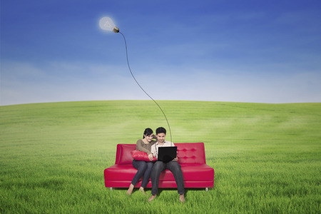 Asian couple using wireless internet with laptop outdoor photo