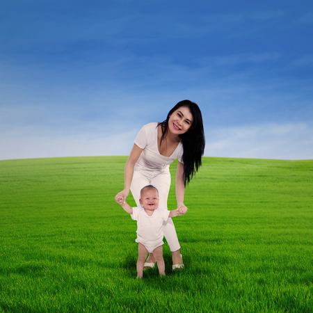 Young mother helping cute baby taking first step in spring green field photo