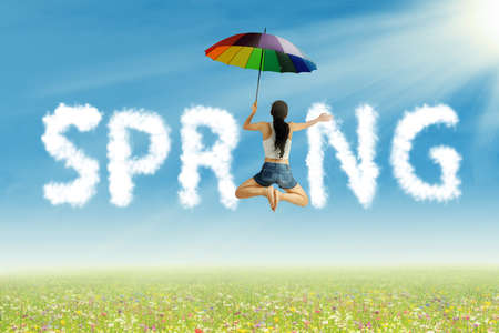 Young woman with colorful umbrella having fun on spring photo