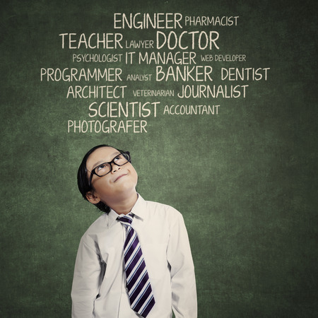 aspirations ideas: Little kid thinking about an aspiration in classroom Stock Photo