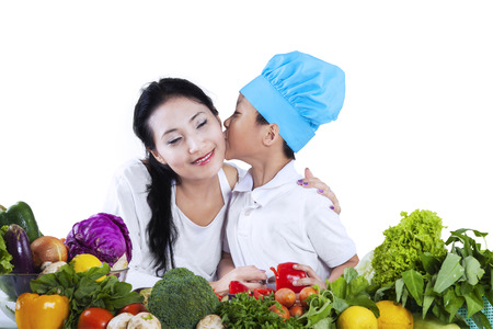 Little chef kissing his mother. isolated on white background photo