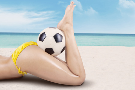 Close up of sexy girls legs with ball. Shoot at the beach photo