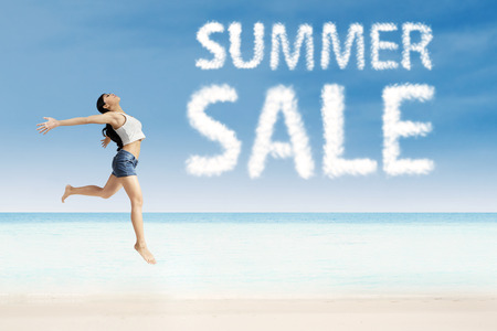 summer sale: Joyful woman jumping on the air with summer sale design Stock Photo