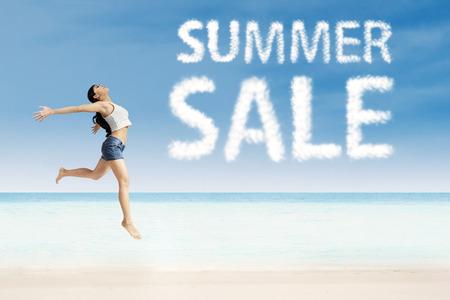 rozradostněný: Radostné žena skákání ve vzduchu s letní návrhu prodeje