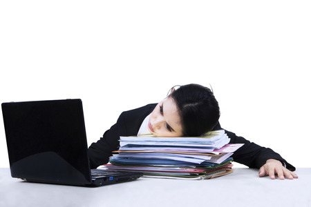 Portrait of overworked business woman take a rest on a pile of documents photo