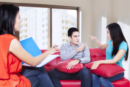 Couple arguing during therapy session with psychologist photo