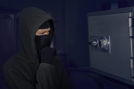 stealing money: Portrait of confused robber thinking the lock code