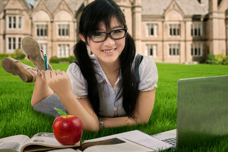 High school student: Female student studying with laptop and book at the park Stock Photo