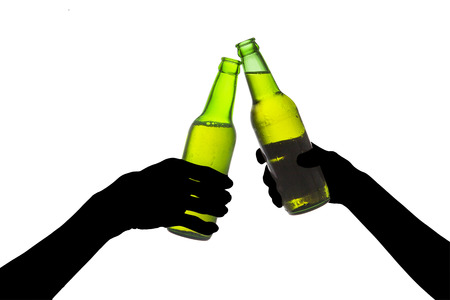 Silhouette of hands toasting with bottles of beer photo