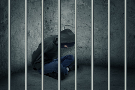 prison break: Catch the burglar concept, thief with balaclava caught and sitting in the jail Stock Photo