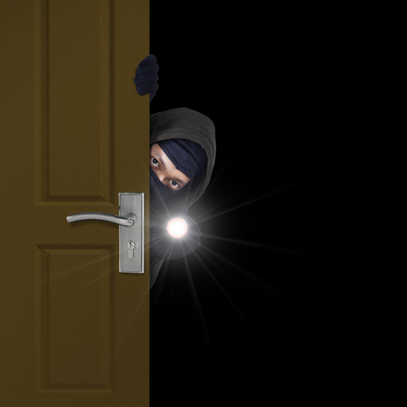 prowler: Burglar sneaking in a open house door during a break and enter past security locks and alarms,