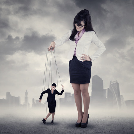 Businesswoman hanging on string and controlled by a businesswoman photo