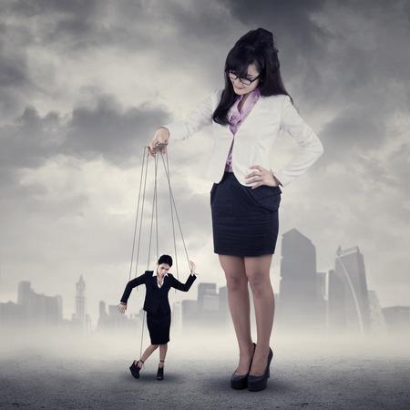 pull toy: Empresaria que cuelga en cuerda y controlado por una mujer de negocios Foto de archivo