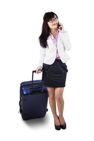 Businesswoman in full length walking with suitcase while talking on the phone photo