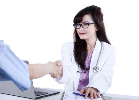 asian doctor: Doctor shaking hands to patient in the office at desk