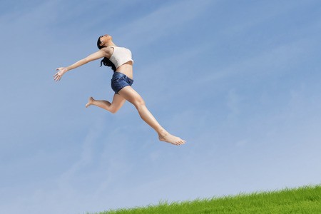 hot pants: Excited woman jumping highly on the nature