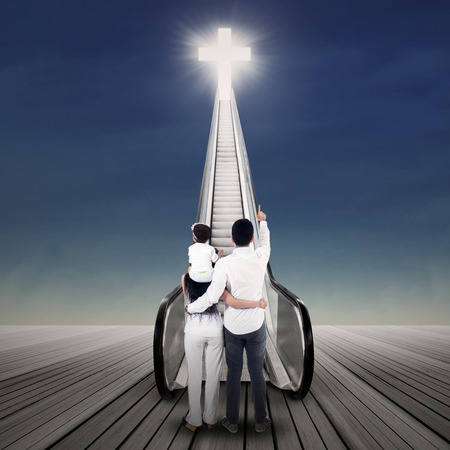 child jesus: Family members are looking at bright cross on the escalator Stock Photo