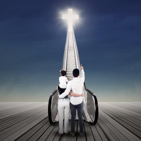 familia cristiana: Los familiares están buscando en cruz brillante en la escalera mecánica