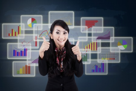 Happy businesswoman giving thumbs up with business interface background photo
