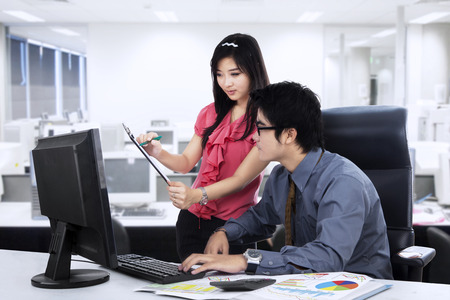 Secretary showing business report to her boss at office photo