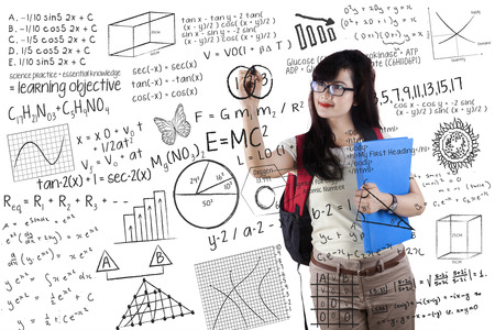 Portrait of female college student using marker to write math formula on the whiteboard photo