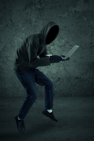 swindled: Criminal in dark clothes and balaclava with the laptop