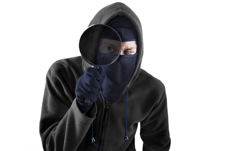Thief using magnifying for looking information. isolated on white background photo