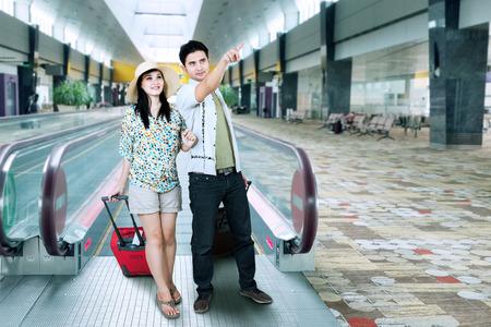 Asian tourist walking on escalator at airport photo