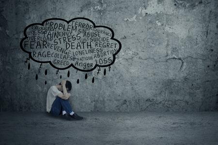 avergonzado: Hombre joven que consigue problemas, sentado y se inclina en la pared con el miedo