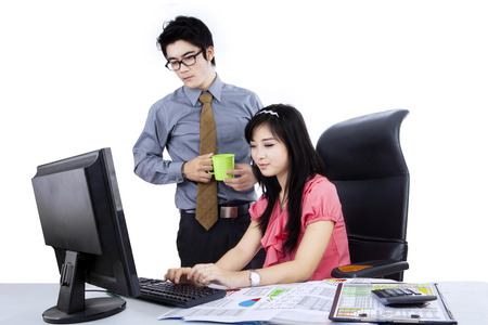 Boss looking at his employee working with computer on the desk isolated over white photo