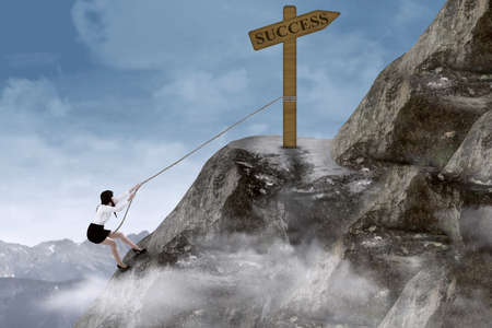 steep cliffs sign: Businesswoman climbing steep mountain with success sign on top