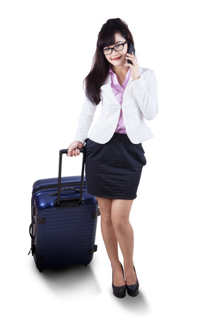 Businesswoman in full length pulling luggage while calling with mobile phone. isolated on white photo