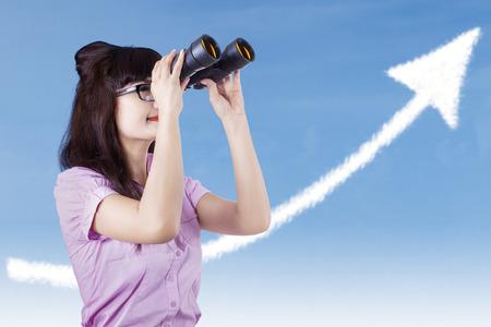 Businesswoman see success cloud with binoculars outdoor photo