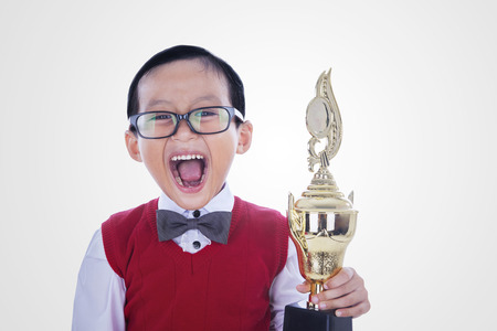 Excited student boy is holding trophy shouting for joy, isolated on white photo