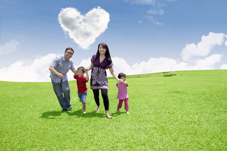 under heart: Asian family is having fun in the park under heart shape clouds Stock Photo