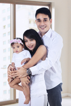Portrait of happy family with baby at the new apartment photo