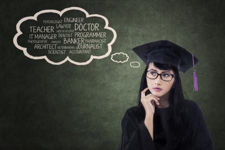 黒板に彼女の夢との卒業の帽子で思慮深い学生