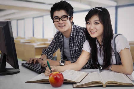 Happy Asian students studying in Library photo