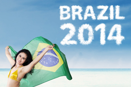 Portrait of a happy pretty woman holding brazilian flag. photo