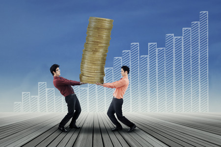Portrait of business team carrying gold coins symbolizing as high profit Stock Photo - 27819370