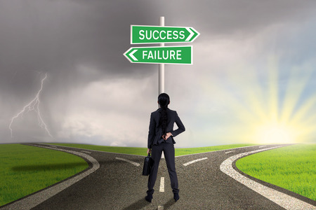 failure sign: Businesswoman is standing on the road with a sign of success or failure Stock Photo