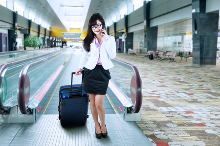 Attractive businesswoman making a phone call at airport photo