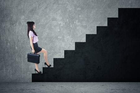 Young businesswoman walking up on stairs photo